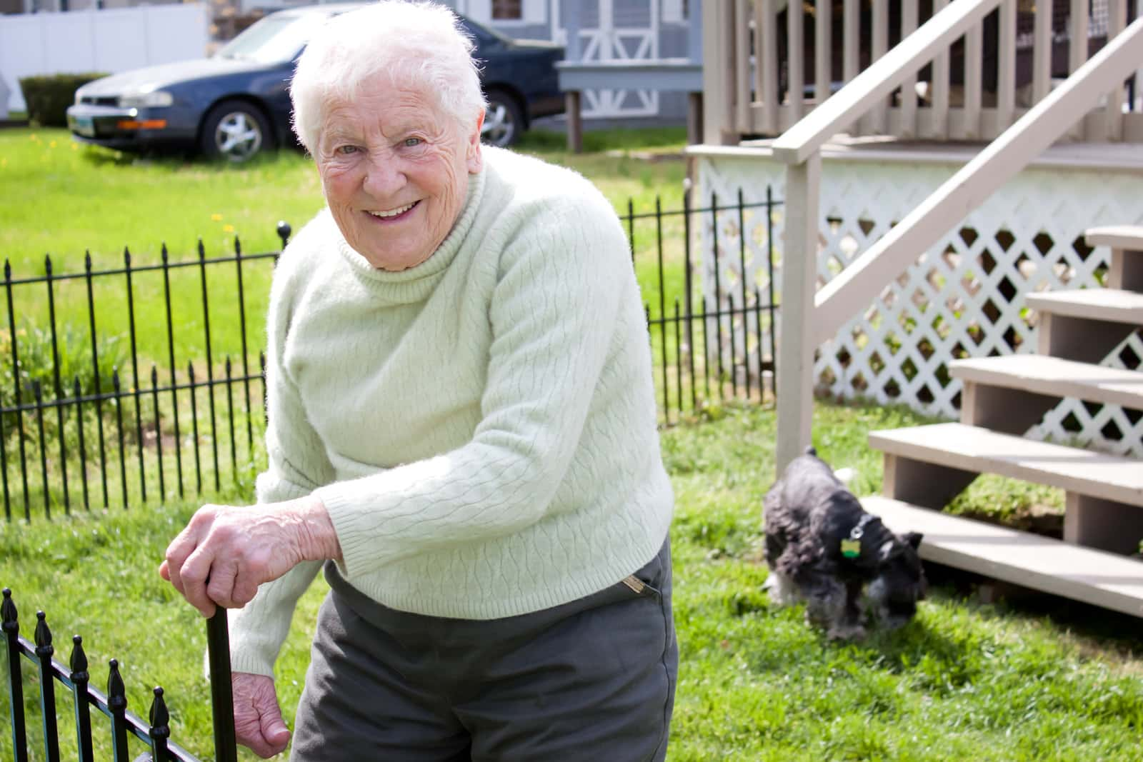 senior lady looking happy with her dog at the bottom of some stairs