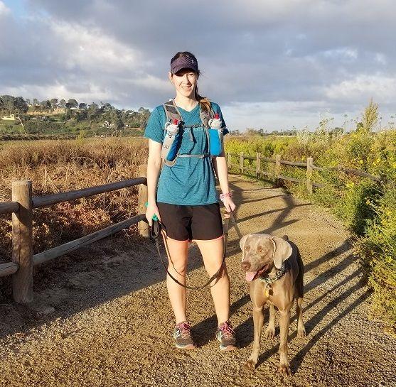 Woman Athlete in shorts and baseball cap with several water bottles on Running Path with Brown Labrador on a leash