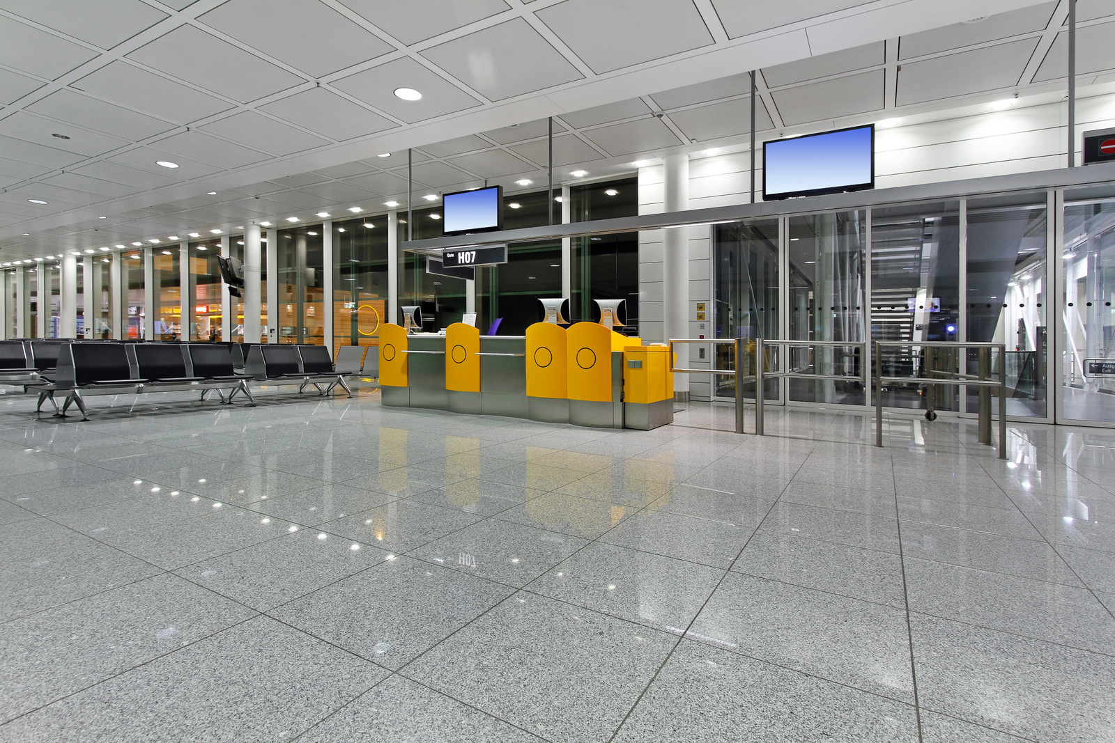 Airport terminal with no people. Gate H07, Shiny floors, rows of empty chairs. Yellow desk at gate but no attendants.